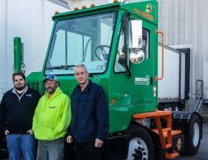 Innovative Transportation Services (ITS) with their new Orange EV T-Series pure-electric terminal truck. From left: James Hotnich, Dispatch Manager; Owen Owens, Driver; and Dave Harper, President of ITS.